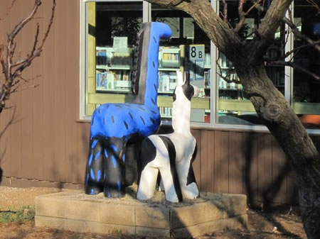 Two animal sculptures look into the window of the Los Altos Library