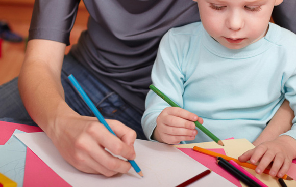 parent showing young child how to hold a pencil for writing and drawing