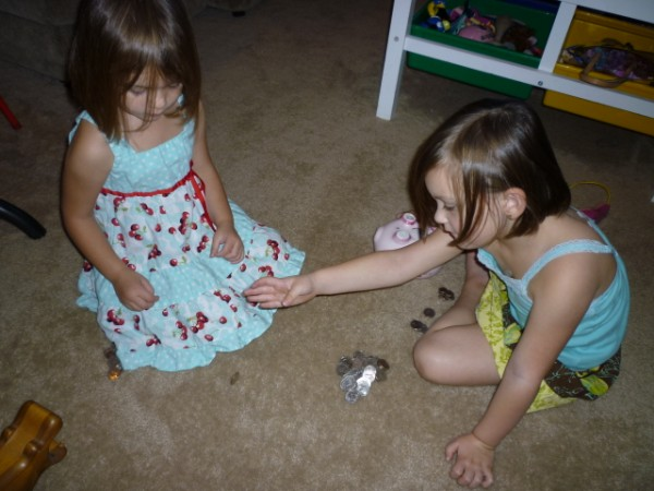two little girls sharing small piles of coins