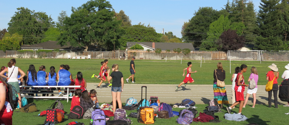 A foot race of middle schoolers on a track, viewed by onlookers