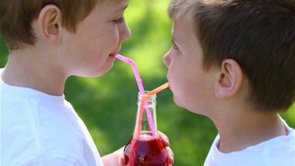 two kids sharing a bottle of soda with two straws