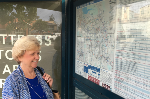 Jeannie Bruins looking at bus stop map by Showers Drive and El Camino. Bus equipment and bus routes have been improved. That's real social justice for the dishwashers, housecleaners, wait staff, students without cars...